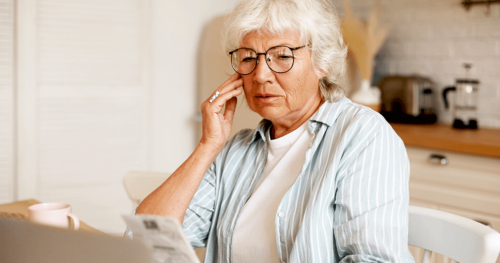 woman holding papers looks concerned; medicare plan finder misleads seniors