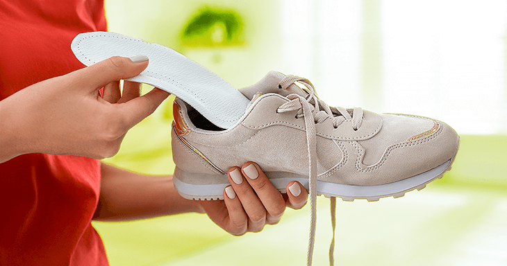 Person inserting orthotic into shoe; Medicare coverage for orthotics